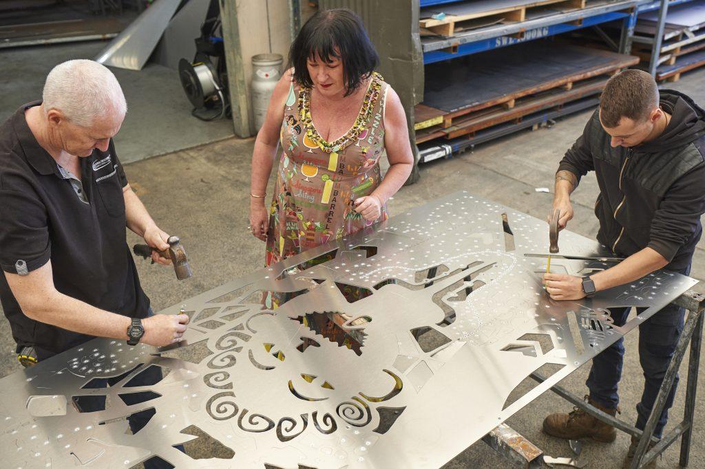 Kanyana employee punching holes in a customized metal art design