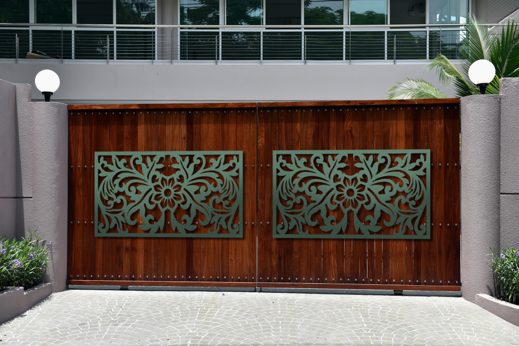 Customized floral metal art installed in front of a wooden gate